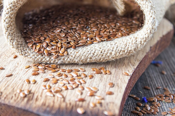 Flax seeds or flaxseed are in a bag on old boards.