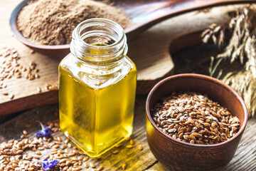 Flaxseed oil in a jar next to flax seeds on a background of old boards.