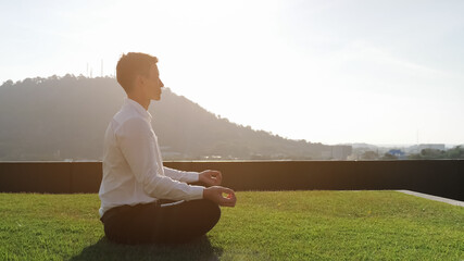 Garden Poster Lotus flower guy in white shirt meditates sitting in lotus pose on hotel terrace grass at sunlight against green hill and blue sky side view copy space