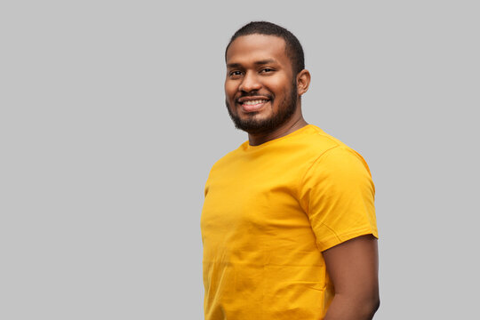 people concept - smiling young african american man in yellow t-shirt over grey background
