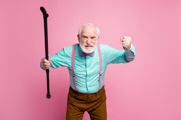 Photo of mad aged man raise walking cane fist angry grimace blaming neighbor kids for noisy behavior wear shirt suspenders bow tie trousers isolated pink pastel background