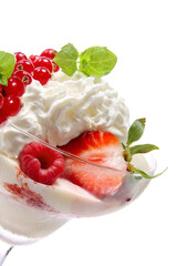Vanilla icecream in vase with strawberries and whipped cream. Closeup, front view
