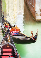 Venice vertical street view cityscape, Italy, Europe.Gondolas at their moorings close-up in water of small beautiful canal. Text copy space in the top side of picture
