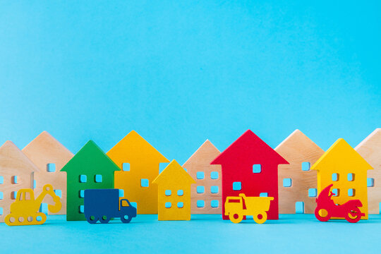Art design picture of nice wooden figures new settlement cottage residence development big large city vehicles riding isolated over bright vivid shine vibrant blue color background
