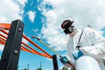 professional specialist in hazmat suit and respirator disinfecting sports ground in park during...