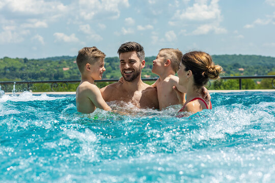 Smiling family of four having fun and relaxing in outdoor swimming pool at hotel resort.