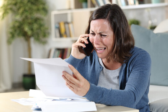 Sad adult woman crying calling on phone with letter at home