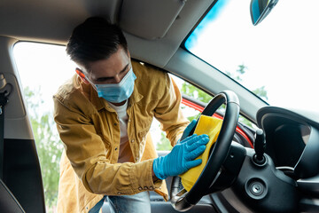 man in medical mask and latex gloves cleaning car interior with rag during coronavirus pandemic