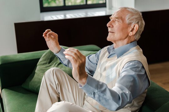 positive senior man meditating with closed eyes on sofa during quarantine