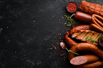 Set of sausage, salami and smoked meat with rosemary and spices on a black stone background. Top...