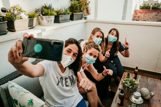 .Group of young girlfriends meeting after the quarantine caused by the covid pandemic19. Taking precaution with the use of surgical masks and taking the first photos together with a smartphone.