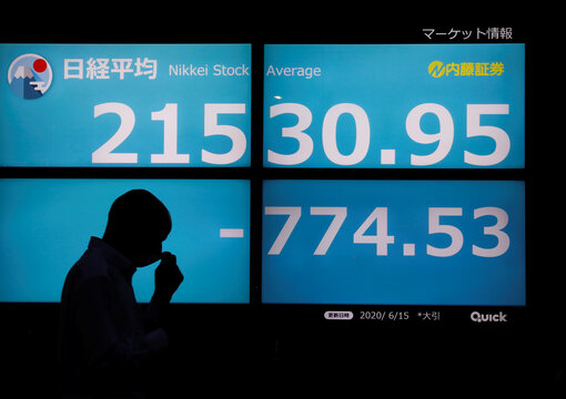 A man wearing a protective face mask, following the coronavirus disease (COVID-19) outbreak, is silhouetted in front of a stock quotation board outside a brokerage in Tokyo