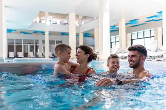 Smiling family of four having fun and relaxing in indoor swimming pool at hotel resort.