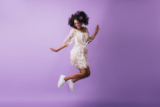 Carefree african girl in white shoes jumping in studio. Adorable female model with flowers in hair dancing on purple background with happy smile.