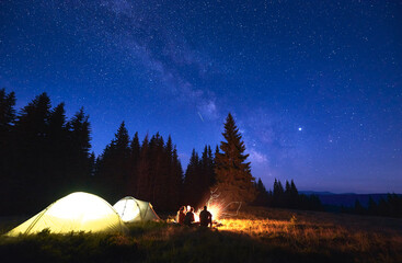 Foto op Canvas Kamperen Night camping with bonfire. People bask in campfire near illuminated tent city, enjoying valley of mountains in pine forest. Dark blue night sky is strewn with bright stars and Milky Way