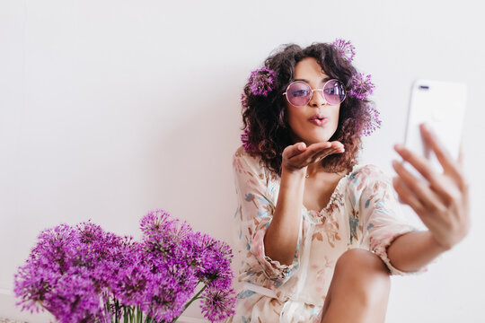 Funny african girl making selfie with kissing face expression in her room. Inspired black young woman sitting beside purple flowers.