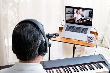 Male piano teacher giving piano lessons online at home using a laptop and smartphone as second camera.