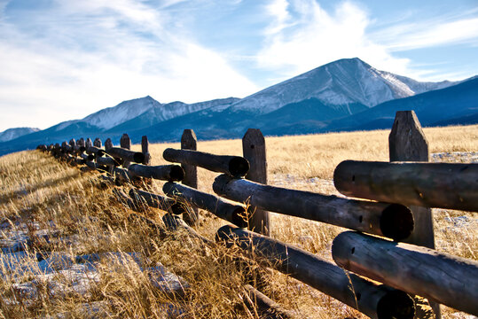 A ranch fence in Colorado with a mountain background.