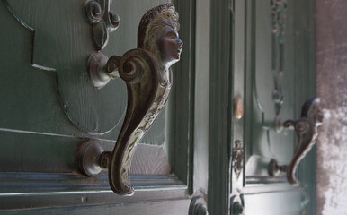 Vintage handles on the green doors in Venice in Italy, closeup shot. Wall mural