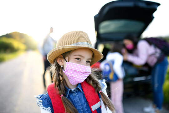 Small girl with family on trip outdoors in nature, wearing face mask.