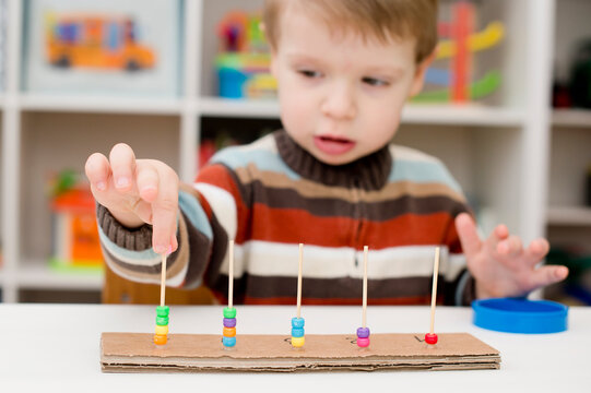 Home made montessori metodic tool for early education, learning to count. 2 year old boy puts beads on wooden rods. Children, people, infancy and education concept. Formation and development of the ch