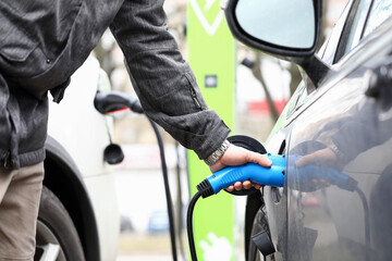 Man fills equipment car tank with fuel gas station