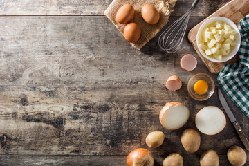 Spanish omelette tortilla ingredients: eggs, potatoes and onion on wooden table top view copy space