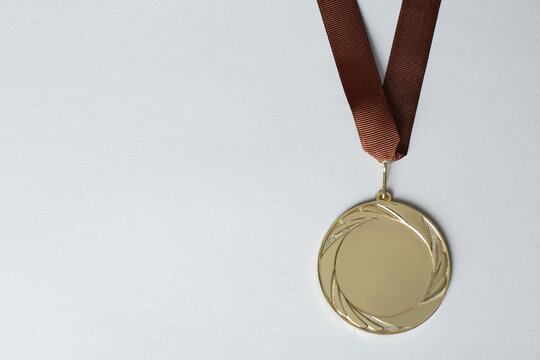 Gold medal on white background, top view. Space for design