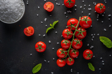 Fresh cherry tomatoes on a black background with spices.  Food background. Top view.