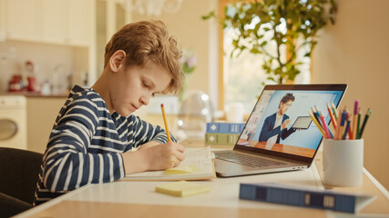 Smart Little Boy Uses Laptop for Video Call with His Teacher. Screen Shows Online Lecture with Teacher Explaining Subject from a Classroom. E-Education Distance Learning, Homeschooling.