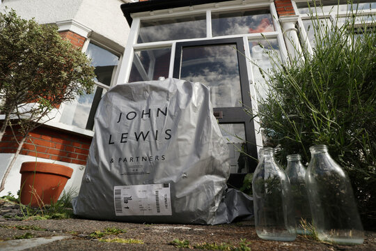 An online delivery package from British retailer John Lewis Partnership is seen on the doorstep of a home in London