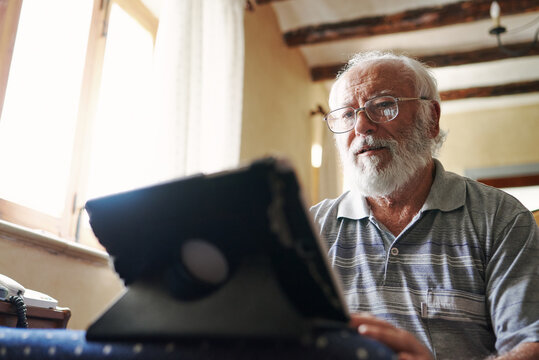 An old man using a tablet
