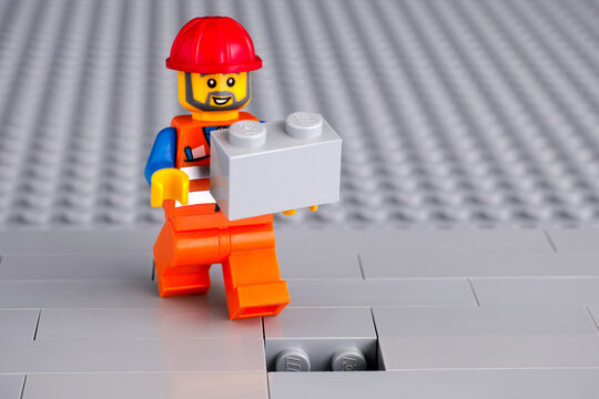 Tambov, Russian Federation - June 06, 2020 Lego construction worker minifigure with gray brick ready to finishing building wall