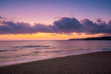 sea scenery at sunset. beautiful landscape of sandy beach in purple dusk. wave running on to the shore. clouds on the  sky above horizon.