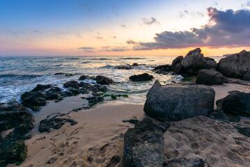 dramatic sunset on the ocean shore. waves crashing rocks on sandy beach. beautiful cloudscape above the horizon