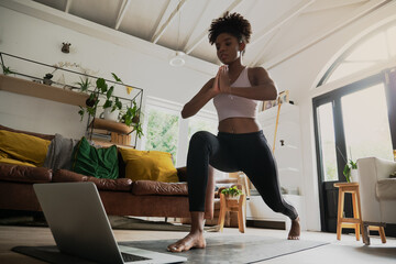 Wide angle shot of young female doing home workout or yoga from home, following an online workout on computer or online