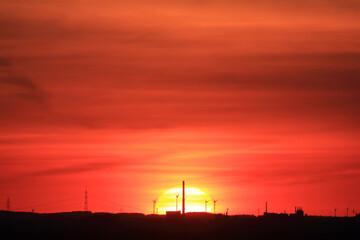 Silhouette einer Industrielandschaft vor roter Sonne