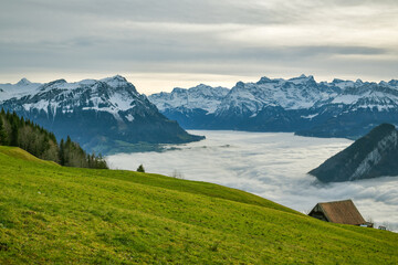 Wall Mural - Clouds covering lakes below majestic Alpine peaks as seen from small meadow above the Sattel
