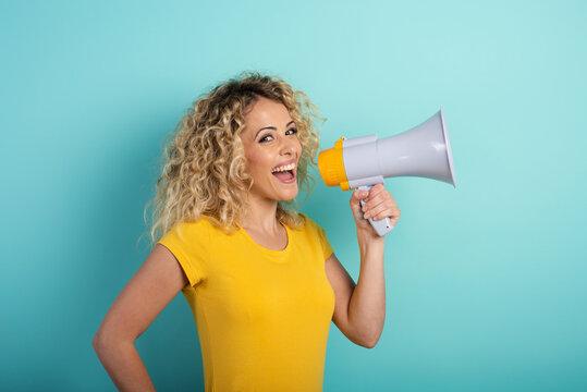 Woman speaks with loudspeaker. joyful expression. cyan background