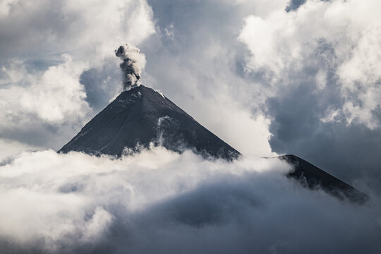 Peak of the Volcán de Fuego throwing smoke and ashes between the clouds around sunset seen from Acatenango. Abstract Guatemalan landscape.