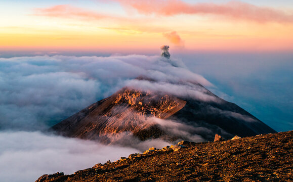 Sunrise with clouds rolling over the summit of Volcan de Fuego in Guatemala seen from the peak of Acatenango.
