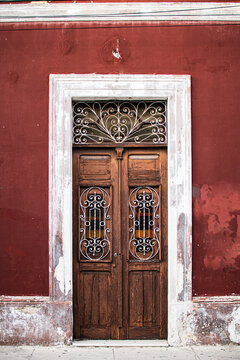 Door of an old colonial building painted in red in Merida,  Yucatan, Mexico.