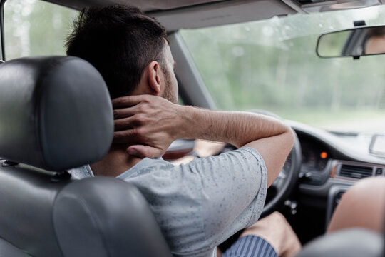 male driver  massages the neck, back and neck pain.
