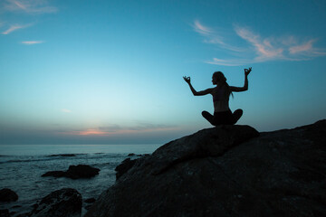 Silhouette of yoga woman sit at Lotus position on the ocean at beautiful dusk.