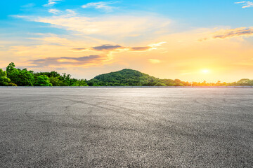 Empty asphalt road and green mountain landscape at sunset.