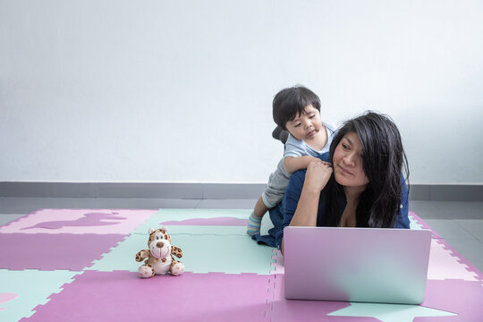 Mexican mother working from home laying at floor and playing with son
