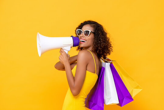 Happy beautiful woman with shopping bags and megaphone on isolated colorful yellow background for sale and discount concepts