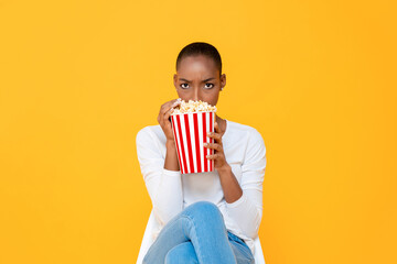 Young scared African American woman watching horror movie and eating popcorn on isolated yellow...