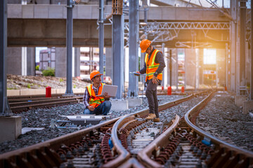 Engineer under inspection and checking construction process railway switch and checking work on railroad station .Engineer wearing safety uniform and safety helmet in work. Fotomurales