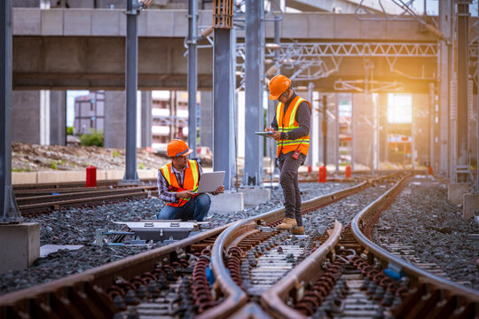 Engineer under inspection and checking construction process railway switch and checking work on railroad station .Engineer wearing safety uniform and safety helmet in work.